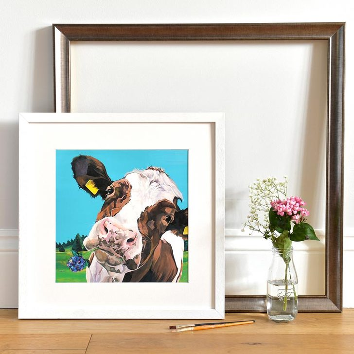 Tilly dairy cow with a flower in her mouth by Lauren Terry