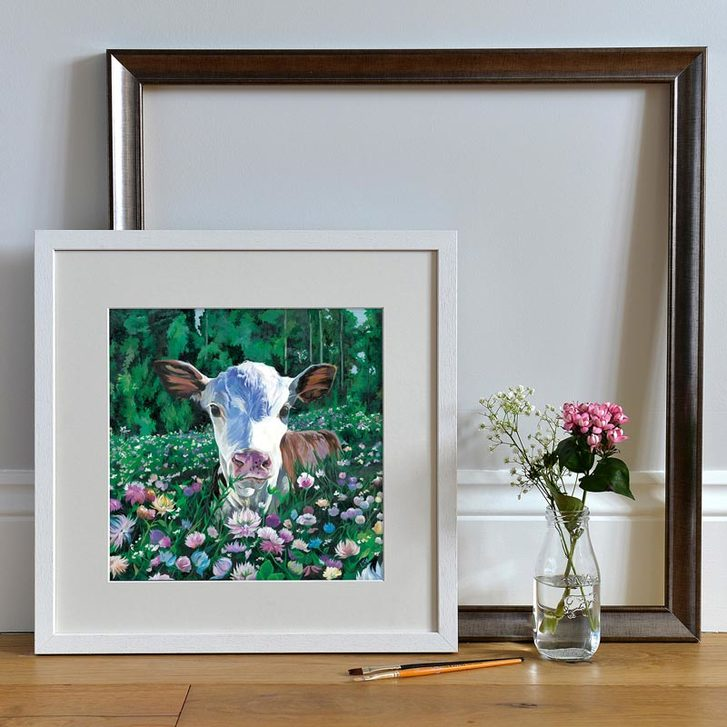 Framed painting of Hereford Calf in field of flowers.